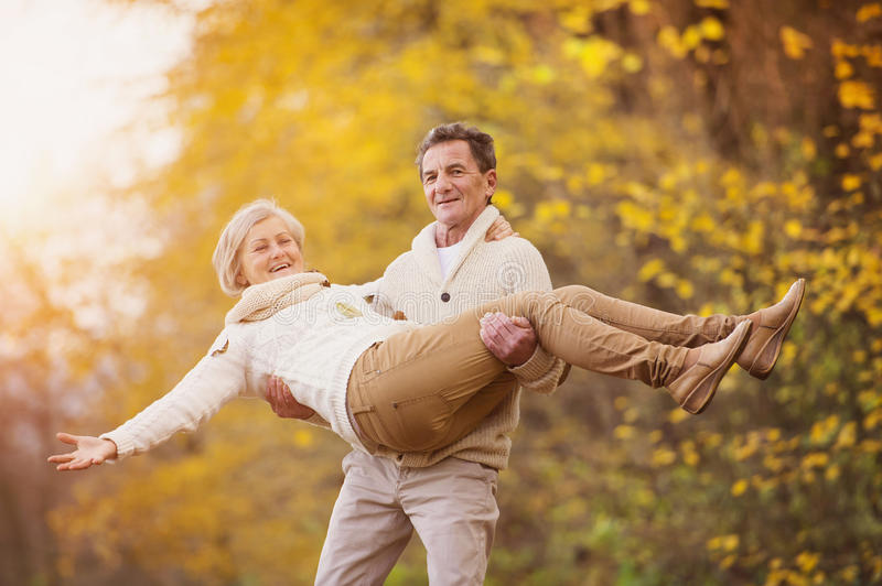 Active seniors having fun in nature. Active seniors having fun and playing with the leaves in autumn forest stock photos
