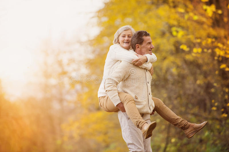 Active seniors having fun in nature. Active seniors having fun and playing with the leaves in autumn forest stock images