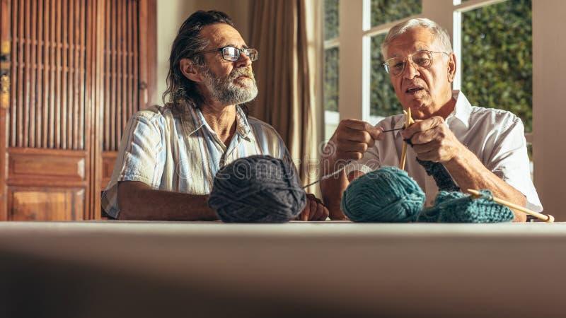 Active seniors knitting at home royalty free stock photography