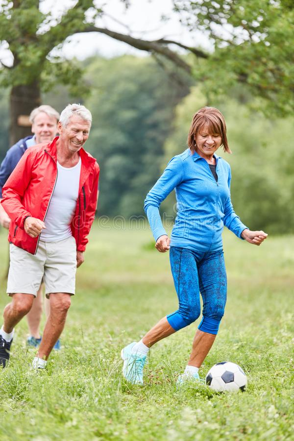 Active seniors play football. Active seniors play soccer in senior sports or at a sports festival royalty free stock photography