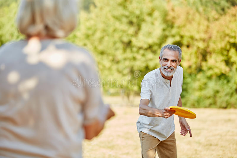 Active seniors playing with a frisbee royalty free stock photos