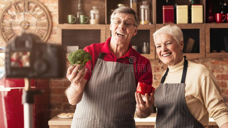 Active seniors recording video about healthy eating. Making vlog content at kitchen royalty free stock photography