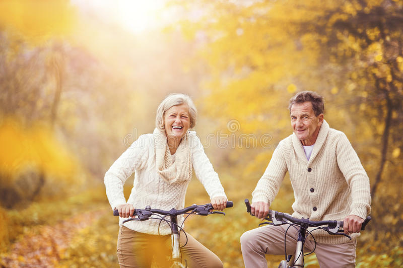 Active seniors riding bike stock photography