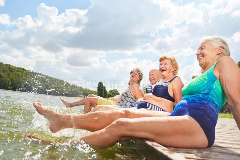 Active seniors splashing with their feet in the water. During a summer vacation at the bathing lake royalty free stock photography