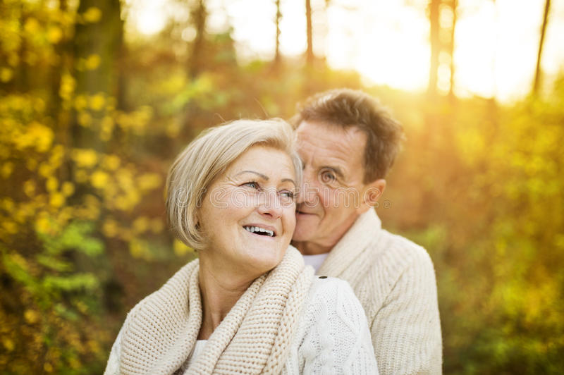 Active seniors taking walk in nature. Active seniors on a walk in a park hugging royalty free stock photography
