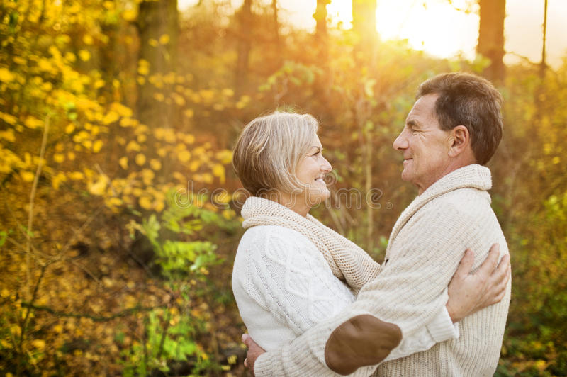 Active seniors taking walk in nature. Active seniors on a walk in a park hugging royalty free stock image