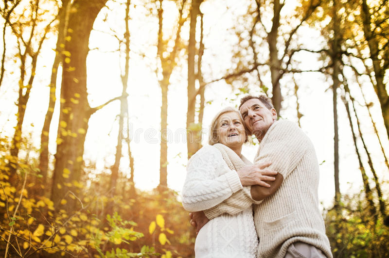 Active seniors taking walk in nature. Active seniors on a walk in a park hugging royalty free stock images