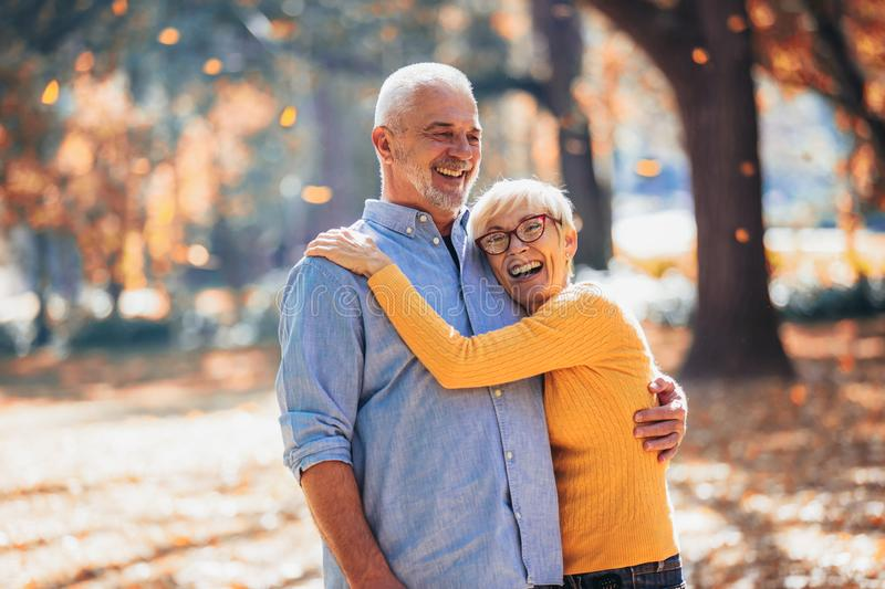 Seniors on a walk in autumn forest stock photo
