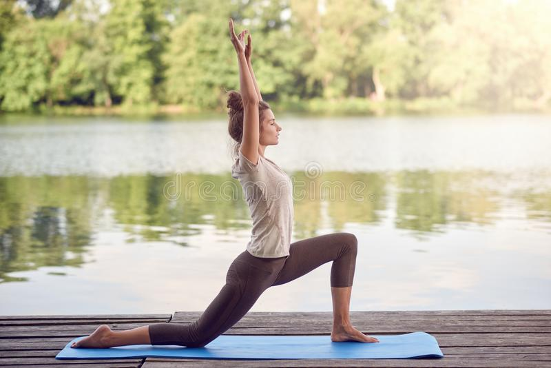 Active slender young woman exercising outdoors royalty free stock images