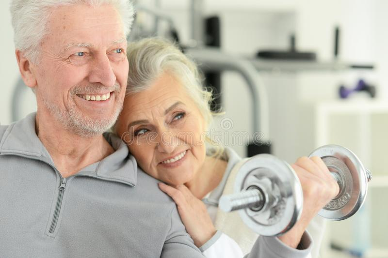 Active smiling senior couple exercising in gym royalty free stock photography