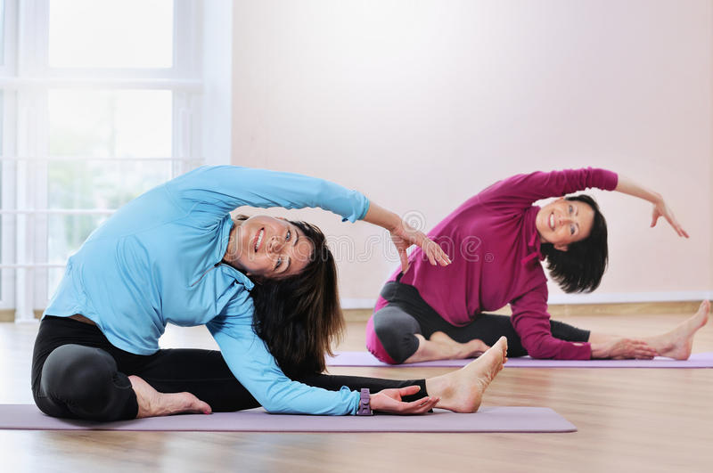 Active sportive mature women doing exercise in fitness studio. Beautiful mature women in sports clothes working out on yoga mat at gym stock images