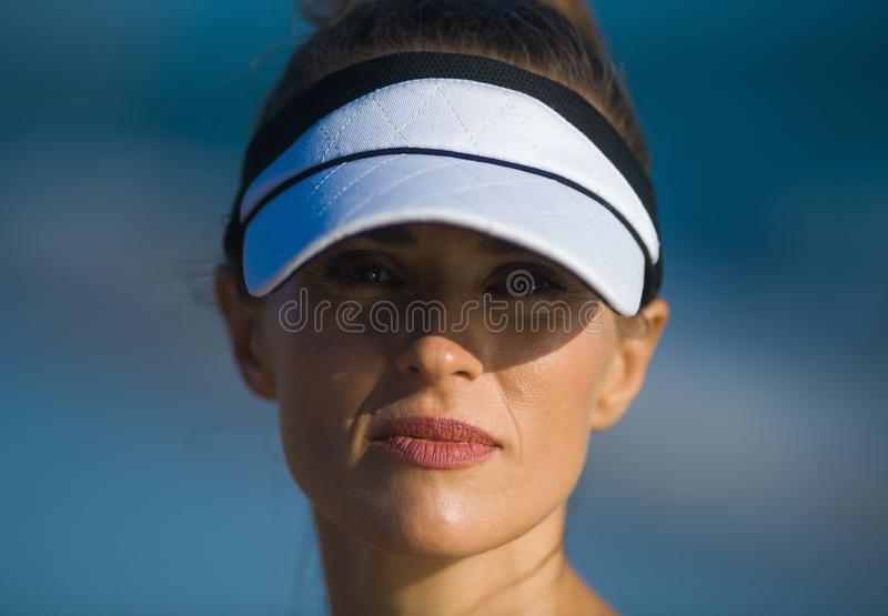 Active sports woman in fitness clothes against blue sea. Portrait of active sports woman in fitness clothes against blue sea royalty free stock image