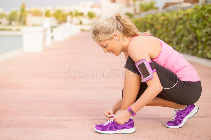 Active sporty girl tying shoes before morning workout stock image