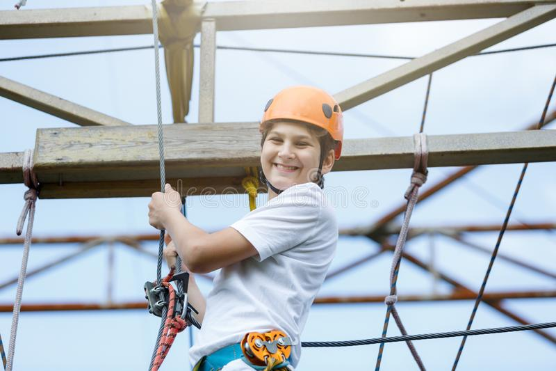 Active sporty kid in helmet doing activity in adventure park with all climbing equipment. Active children climb on the trees. And having fun outdoors. Summer royalty free stock photo
