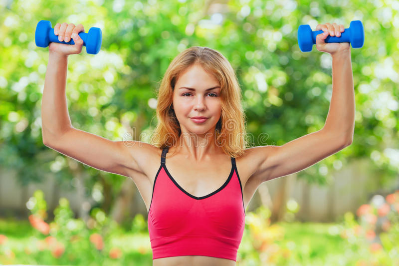 Active sporty woman doing morning exercises with dumbbells at home royalty free stock image