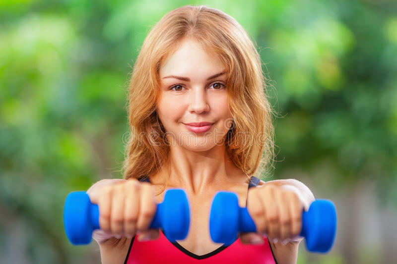 Active sporty woman doing morning exercises with dumbbells at home stock images