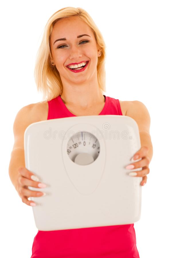 Active sporty woman holds a scale as she lost weight stock photography