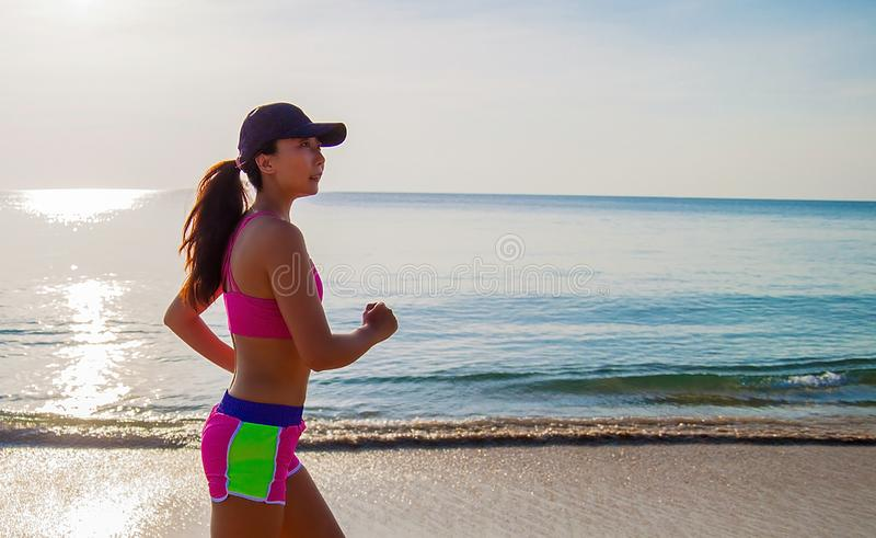 Woman fitness, jogging workout and sport activity on summer holiday.. Active sporty woman run along ocean surf by water pool. Sunset sand beach background with royalty free stock photography