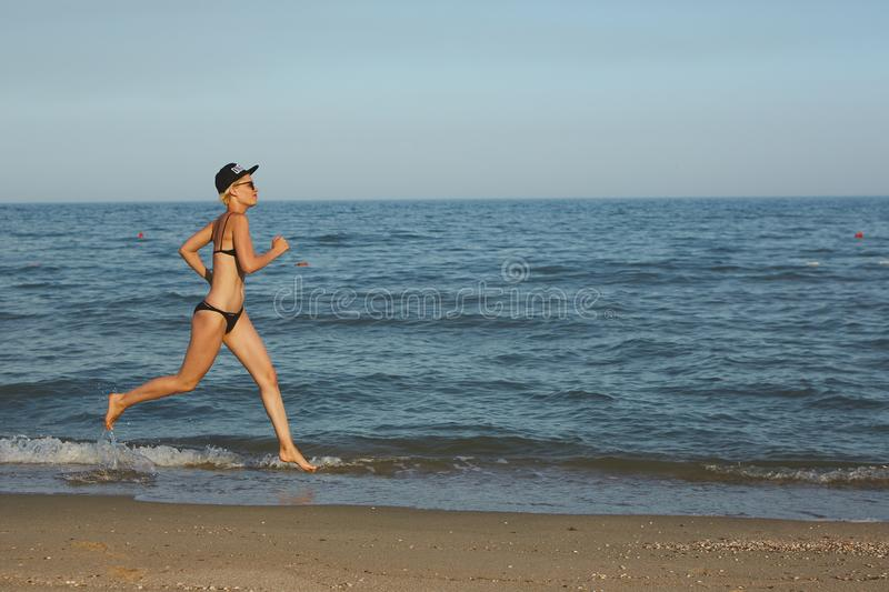 Active sporty woman run along ocean surf by water pool to keep fit and health. Sunset black sand beach background with royalty free stock images