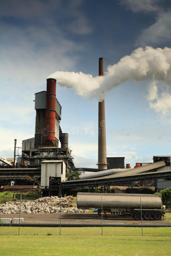 Active steel mill smelter emiting billowing toxic fumes. Steel mill smelter emitting toxic fumes and air pollutants billowing up and out of one of its many tall stock photography