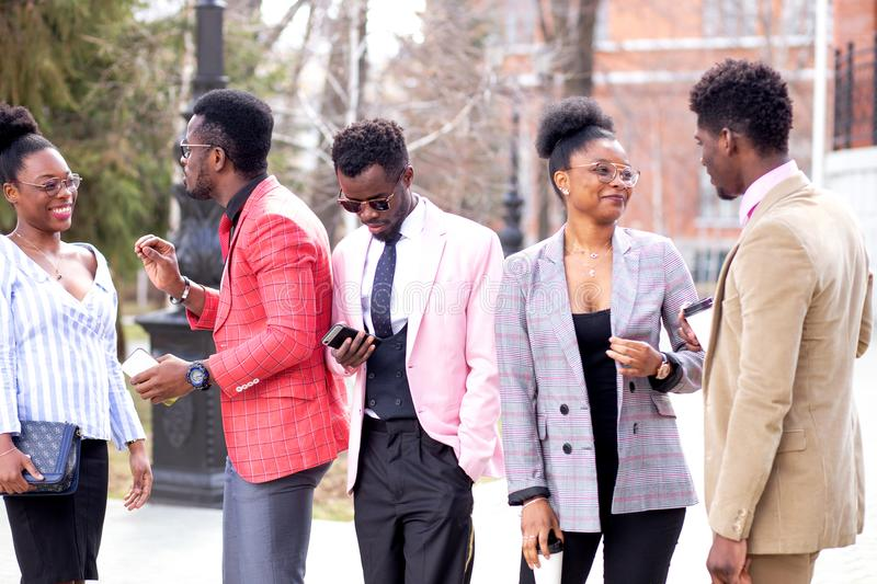 Active street discussions of afro people. Two black couples are flirting while the men in white suit is making a phone call stock images