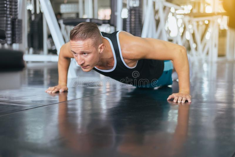 Active strong man doing push up and exercises on floor at gym stock images