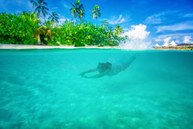 Active summer vacation. Young active woman diving near Maldives island, enjoying marine life, swimming with pleasure in the Indian sea, summer vacation concept stock photography