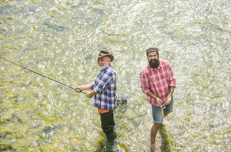 Active sunny day. Fishermen fishing equipment. Hobby sport activity. Fishermen friends stand in river. Fish normally royalty free stock images
