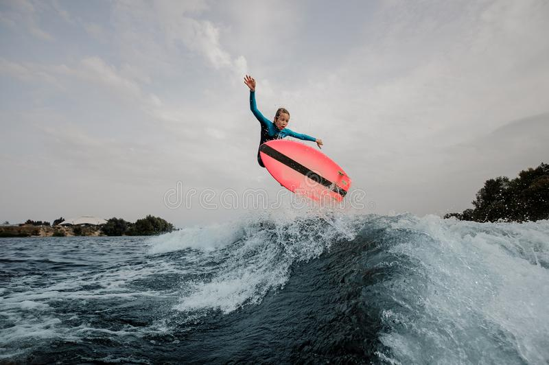 Active teenager boy jumping on the orange wakeboard stock photography