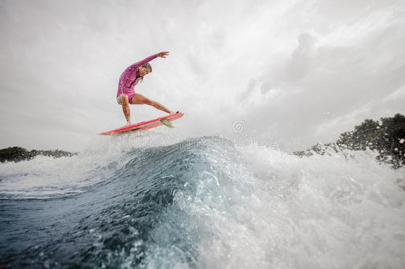 Active teenager girl jumping on the orange wakeboard on the rive royalty free stock photography