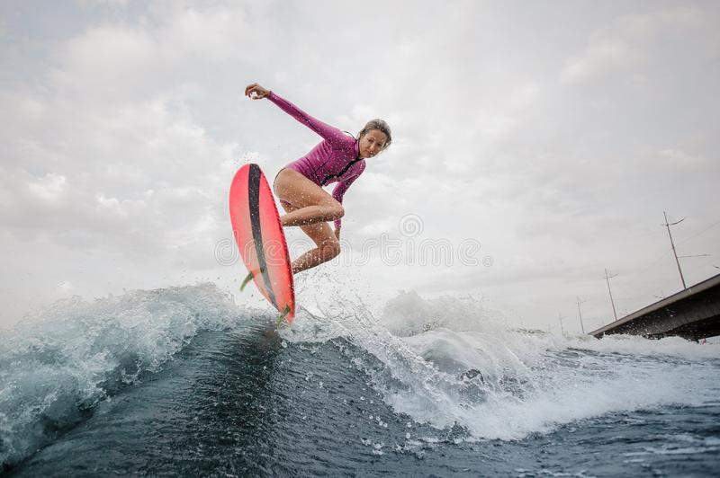 Active teenager girl jumping on the wakeboard royalty free stock photography