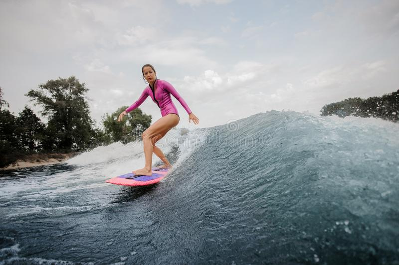 Active teenager girl standing on the orange wakeboard royalty free stock images