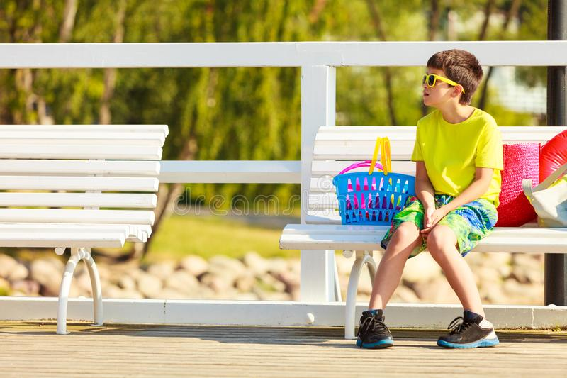 Boy sitting on bench with toys. stock photo
