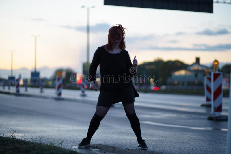 Active traveler dancer woman performing on a road construction site at sunset time with car lights passing by wearing royalty free stock image