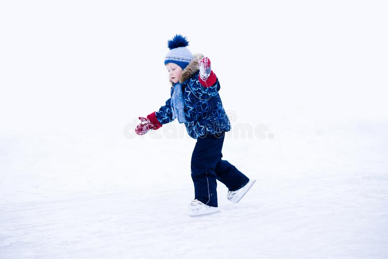 Active winter holiday - cute little boy skating on an ice rink.  stock photo