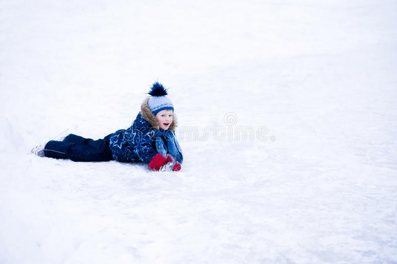 Active winter holiday - cute little boy skating on an ice rink.  stock images