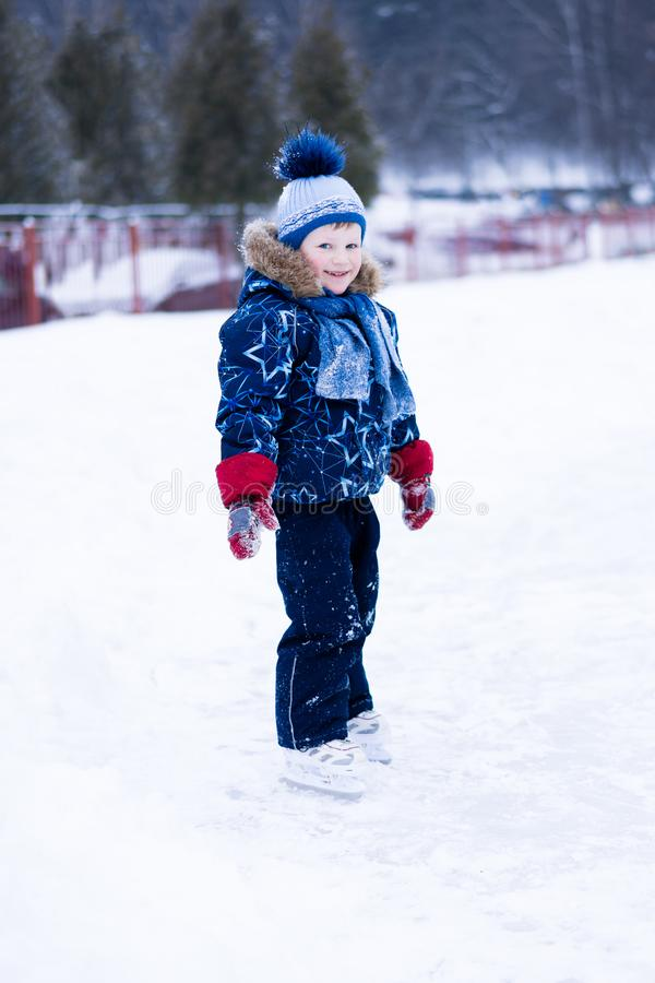 Active winter holiday - cute little boy skating on an ice rink.  stock photos