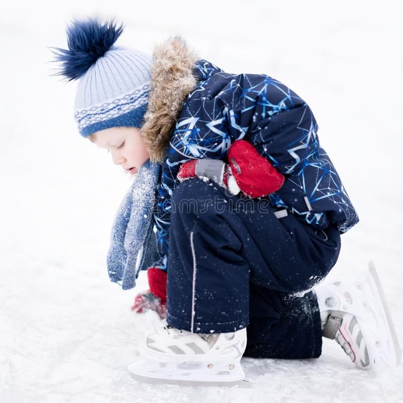 Active winter holiday - cute little boy skating on an ice rink.  royalty free stock photography