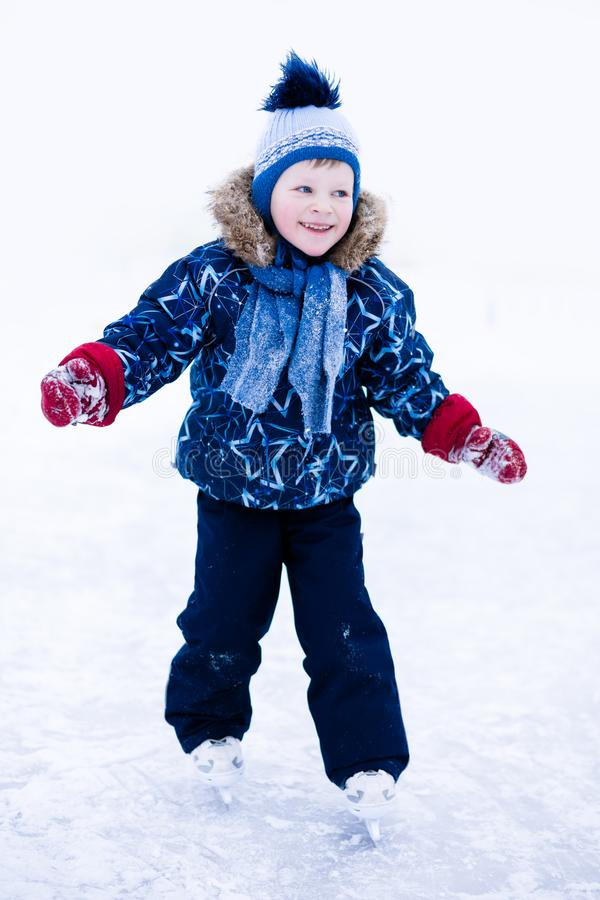 Active winter holiday - cute little boy skating on an ice rink.  royalty free stock photos