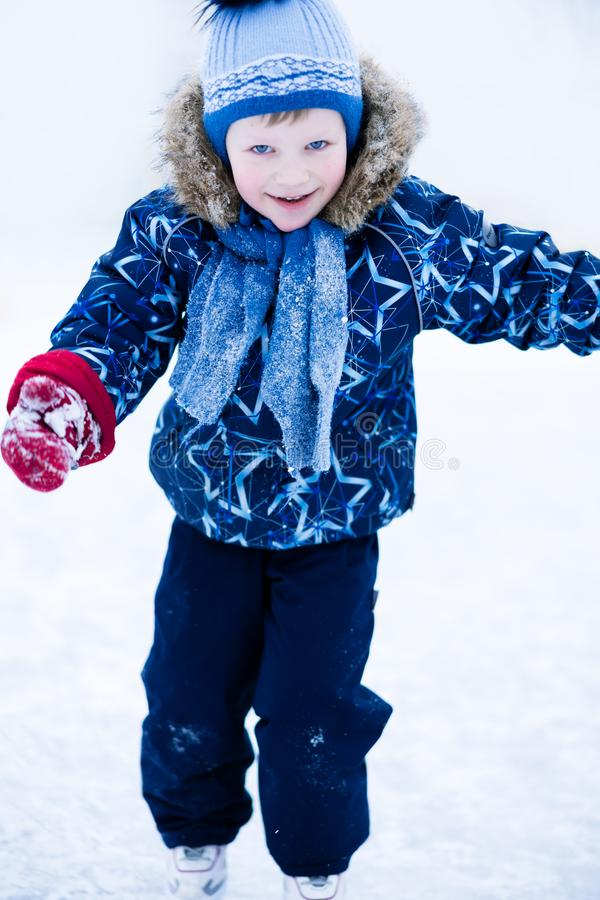 Active winter holiday - cute little boy skating on an ice rink.  stock image