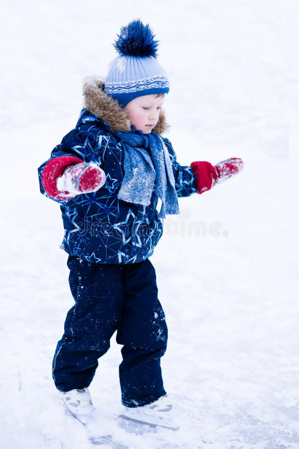 Active winter holiday - cute little boy skating on an ice rink.  royalty free stock image