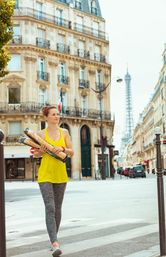 Active woman with 2 French baguettes crossing street. Active woman in sport clothes with 2 French baguettes crossing street not far from Eiffel tower in Paris royalty free stock images