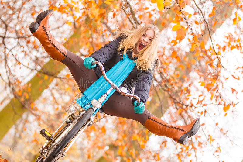 Active woman having fun riding bike in autumn park. Happy carefree active woman having fun riding bike bicycle in fall autumn park. Crazy young girl relaxing royalty free stock image