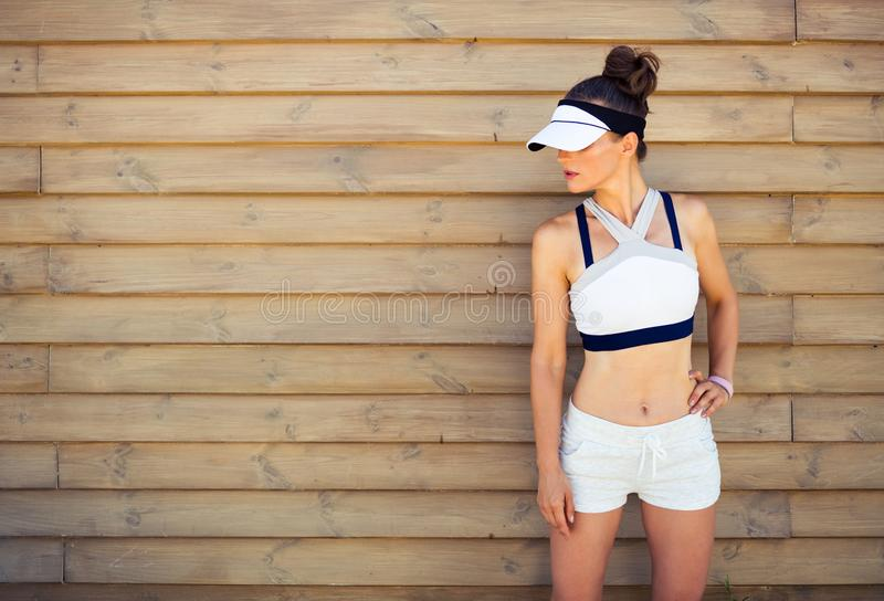 Active woman jogger looking at copy space against wooden wall royalty free stock image