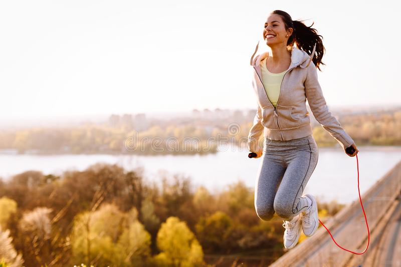 Active woman jumping with skipping rope outdoors. Active young woman jumping with skipping rope outdoors stock photography