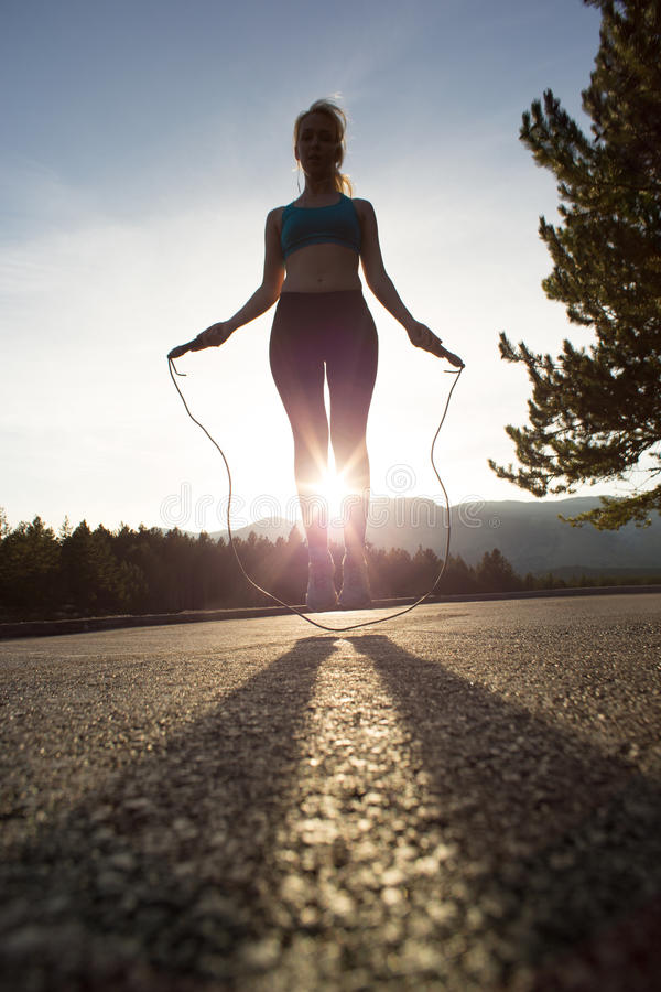 Active woman jumping with skipping rope stock photo