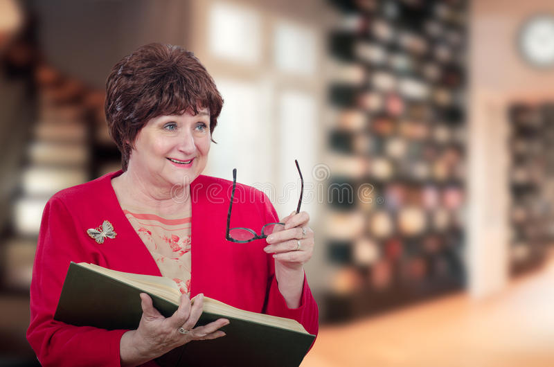 Active woman professor laughs with book stock image