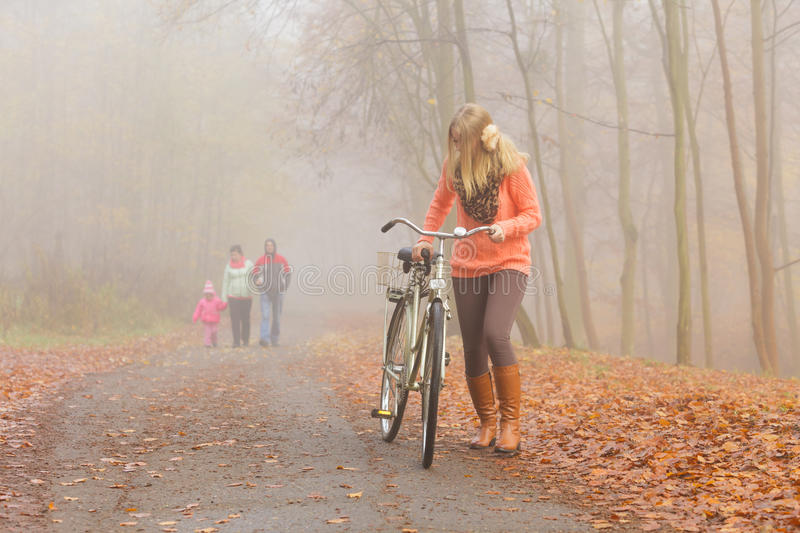 Active woman riding bike bicycle in autumn park. royalty free stock image