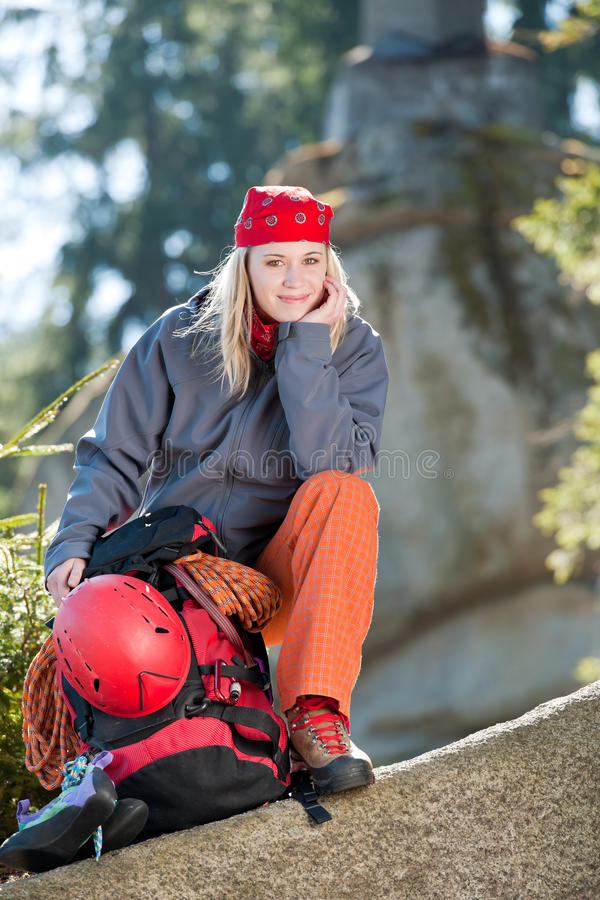 Active woman rock climbing sitting backpack royalty free stock photography