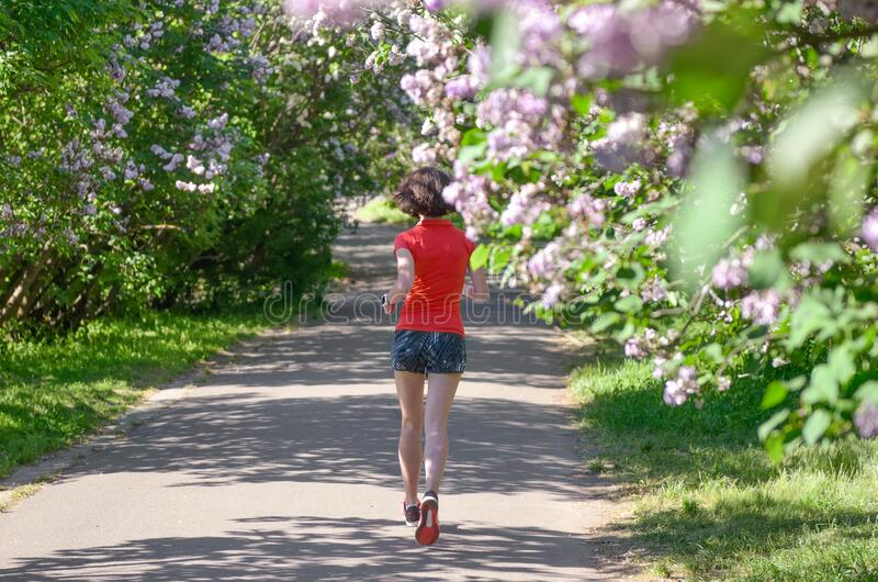 Active woman runner running in spring park with lilac blossom, morning run outdoors, fitness jogging healthy lifestyle stock images